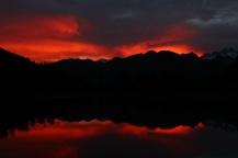 flaming sunrise above mirror Lake Matheson
